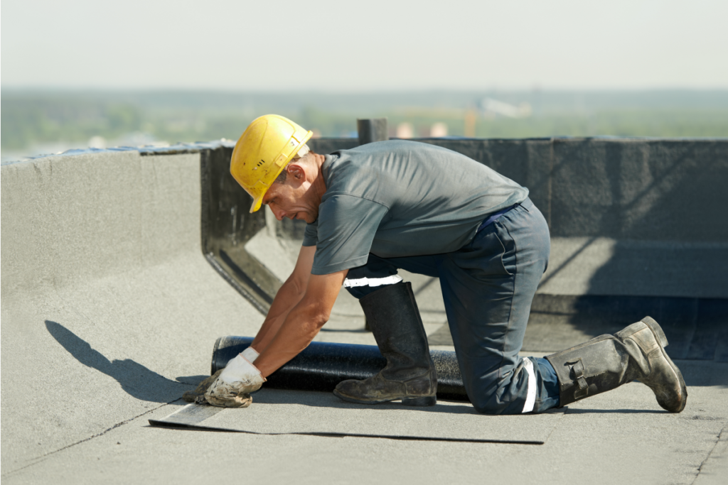 Technician inspecting damage to commercial roofing