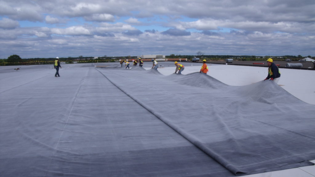 Technicians installing a membrane commercial roofing system