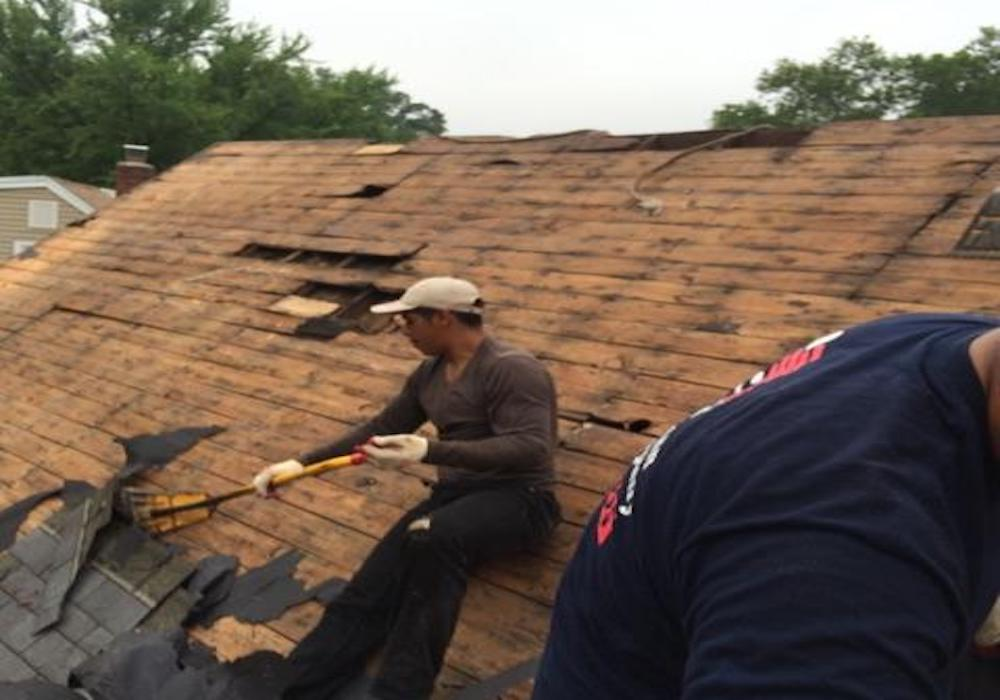 Roofers removing layers of roof in preparation