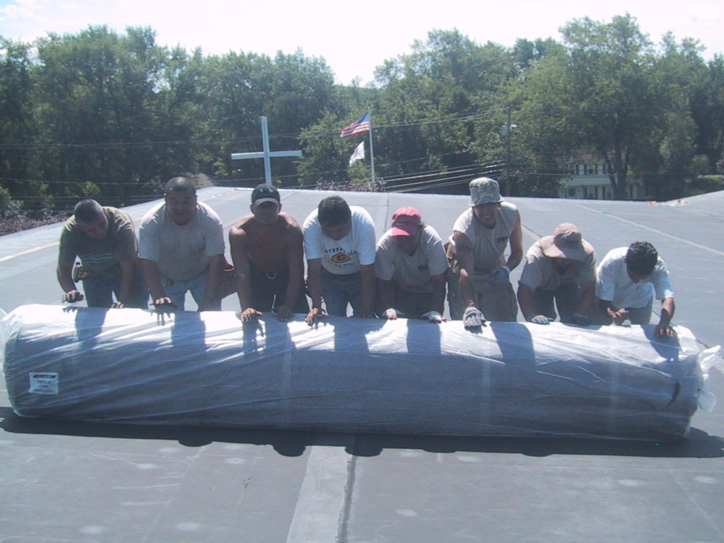 Commercial roof replacement costs can be affected by the materials chosen. Workers roll out roofing material on a roof.
