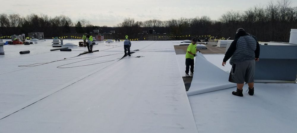 TPO roof installation - Workers lay sheets of TPO on a commercial roof