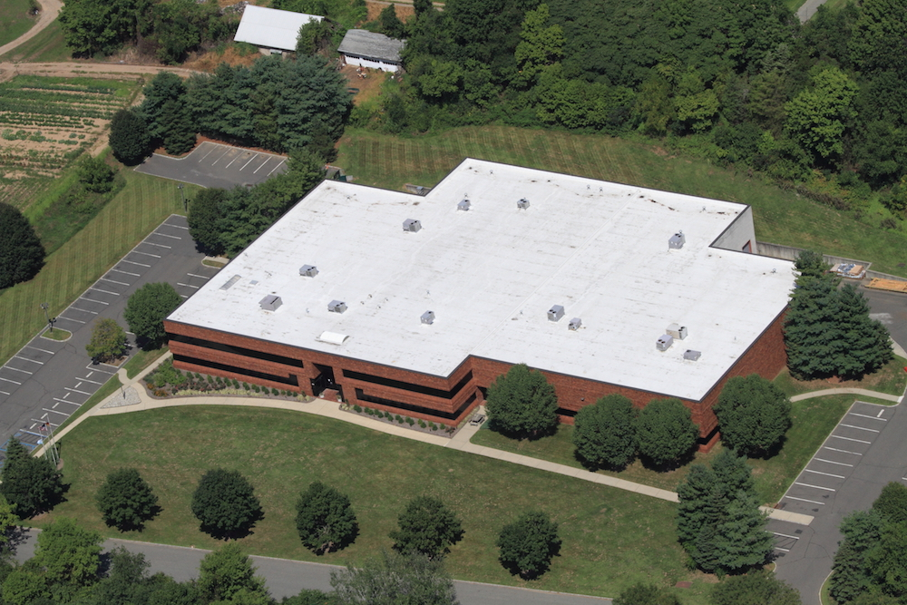 A large, flat commercial roof with several protrusions can increase commercial roof replacement costs.